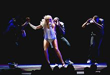 A blond woman performs onstage. She is clad in a white leotard. She is singing onto a microphone in her left hand. Her right hand is held by somebody whose appearance is not clear. On her left, two African dancers imitate a pose where they appear to be looking at the woman throuogh a camera.