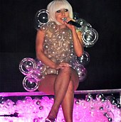 A blond woman in a bob-cut, sitting cross-legged on a transparent platform which is full of bubbles and lit from inside in pink. The woman is wearing a dress made of transparent bubbles of varying sizes. She is holding a microphone in her left hand and appears to be smiling.