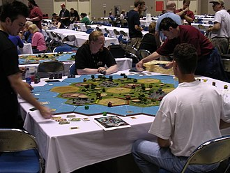 Catan - A giant game of Settlers being played at Gen Con Indy 2003. This is one of many Settlers of Catan custom, extra-large boards seen during demonstrations and tournaments at Gen Con.