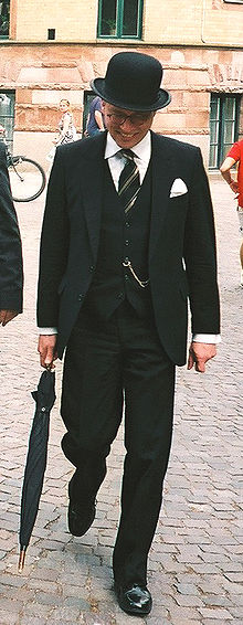 A man in a three-piece suit with a bowler hat, glasses and an umbrella.
