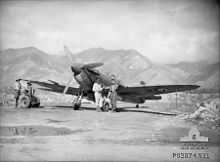 Three men stand near a propeller aircraft on a runway. There are tall mountains in the background.