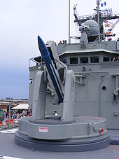 Close up of a naval missile launcher. A blue missile with white fins has been loaded.