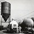 HUA-169553-Afbeelding van het overladen van cement van een silowagen van de N.S. naar een vrachtauto van Usilo op de laad- en losplaats van het N.S.-station Bilthoven te De Bilt.jpg