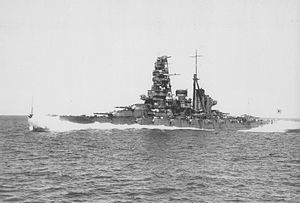 A portside view of Haruna – a large warship with a tall superstructure and two funnels – steaming at full speed in high seas with waves coming over the bow