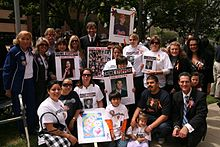 Henry Nicholas (center), his mother, Marcella Leach (standing, far left),Crime Survivors founder Patricia Wenskunas (standing, fifth from left), victims' rights advocate Collene Campbell (standing, second from right) and former Orange County Deputy District Attorney Todd Spitzer (seated, far right) join with victims and families in downtown Los Angeles to commemorate the annual National Day of Remembrance for Murder Victims.