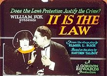 A man and woman in formal dress, with advertising text: 'Does the Law's Protection Justify the Crime? / William Fox presents It Is the Law / From the stage play by Elmer L. Rice / Based on the story by Hayden Talbot / A J. Gordon Edwards production'