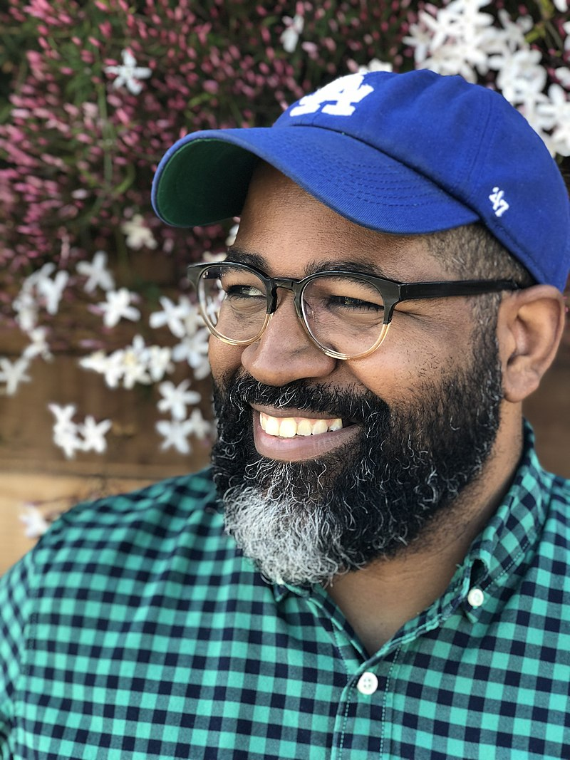 Headshot of Jamil Smith. He wears glasses, a green-and-black checked collared shirt and a blue Los Angeles Dodgers cap. He smiles, looking off-camera.