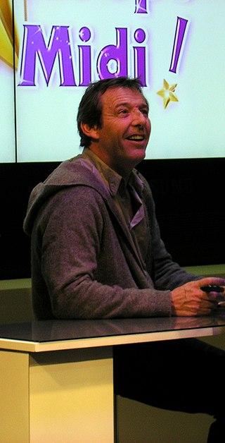 Jean-Luc Reichmann sur le stand TF1 du Mondial de l'automobile de Paris 2012, pavillon 2.2 du Palais des Congrès de la Porte de Versailles, Paris | Source : Wikimedia.