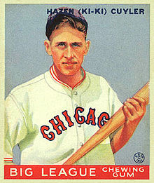 "A baseball card of a man holding a baseball bat with both hands while wearing a white baseball jerseys with ""Chicago"" written across the chest in blue-bordered red letters and a blue cap."