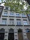 foto van Drie verdiepingen tellend pand onder zadeldak met witgepleisterde gevel, bekroond door een verhoogd, driehoekig doorbroken fronton met tandlijst en obelisk