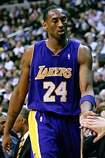 "A man, wearing a purple jersey with a word ""LAKERS"" and the number ""24"" written in the front, is standing in front of the crowd."