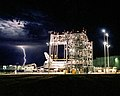 Lightning strikes in the distance as the Space Shuttle Discovery receives post-flight processing in the Mate-Demate Device. Original from NASA. Digitally enhanced by rawpixel. (31411976957).jpg