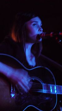 18-year-old Mitchell is shown in an upper body shot. She plays a guitar while singing into a microphone. She is tinged blue-white due to lighting and her right hand, which is strumming the guitar strings, is blurred.