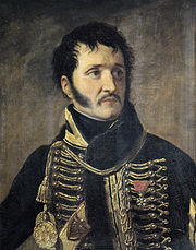 Painting of a black-haired man with long sideburns and a moustache. He wears a dark hussar-style uniform with yellow frogging.