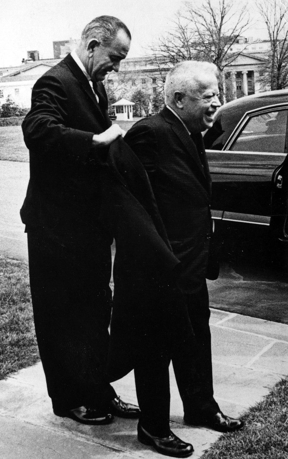 Lyndon B. Johnson helps David Dubinsky put on his coat.