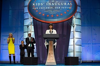 Second inauguration of Barack Obama - First Lady Michelle Obama delivers remarks during the Kids' Inaugural Concert at the Walter E. Washington Convention Center. Second Lady Jill Biden (left) stands in the background.