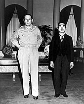 A tall Caucasian male (MacArthur), without hat and wearing open-necked shirt and trousers, standing beside a much shorter Asian man (Hirohito) in a dark suit.