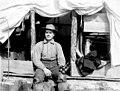 Man seated in doorway of framed tent, holding binoculars, Inland Passage, circa 1906 (AL+CA 7604).jpg
