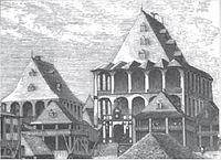 a cluster of rectangular wooden buildings with peaked rooftops, the largest of which crowns the hill and is surrounded by wooden verandas on each of its three stories