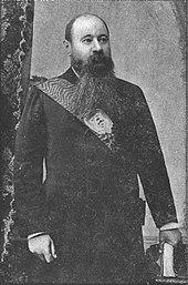 En mand med et enormt mørkt skæg iført et statsskærm
