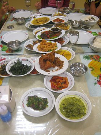 Nasi Padang - The hidang style serving in a Padang restaurant, the table in front of customer is filled with various rich-flavored and spicy Padang dishes