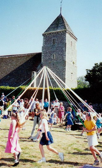 May Day - Maypole dancing at Bishopstone Church, East Sussex, in England, UK.