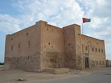 sand coloured square castle with flag flying