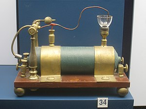 Induction coil - Early coil by Charles G. Page, 1838, had one of the first automatic interrupters. The cup was filled with mercury. The magnetic field attracted the iron piece on the arm (left), lifting the wire out of the cup, breaking the primary circuit.