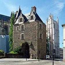 Grande bâtisse en pierre surmontant un porche; au second plan, la cathédrale.