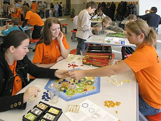 Catan - Three young women playing a game of Catan in a school