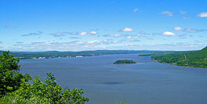 Newburgh Bay - Newburgh Bay from Storm King Mountain. Bannerman's Island is in the front. New Windsor, the city of Newburgh and the bridge are visible, with the Shawangunks and Catskill peaks around Slide Mountain in the distance.