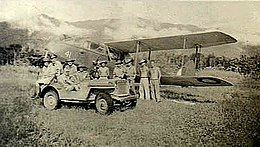 Military personnel and a jeep in front of a twin-engined biplane, with jungle and a mountain range in the background