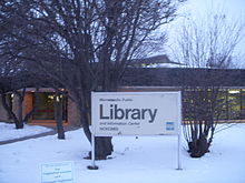 "large sign saying ""Library"" in front of Nokomis Library lit from inside at night"