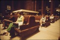PASSENGERS SIT ON MASSIVE WOODEN BENCHES WHICH FIT IN WITH THE ARCHITECTURE OF THE CAVERNOUS CHICAGO UNION STATION.... - NARA - 556070.tif