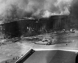 A burning hangar with destroyed planes scattered in front