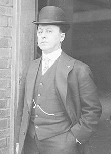 Medium balck and white shot of white man standing in a doorway wearing a dark suit and derby hat