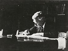 A black and white portrait of James Dugald Somerville writing at a desk circa 1933
