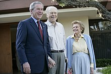 President Bush in a suit standing next to the Fords in casual attire in front of their yellow house.