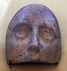 Partie haute d'un masque ovale en céramique où sont visibles les yeux et le nez.