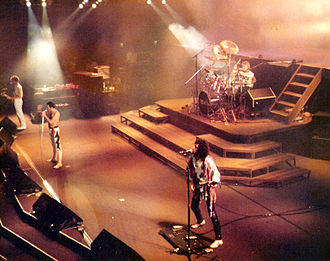 Lead vocalist - Queen performs in a typical rock band layout during a 1984 concert. Lead singer (front man) Freddie Mercury stands centre-stage in front of drummer Roger Taylor and positioned between bass guitarist John Deacon and lead guitarist Brian May.