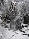 A very tall waterfall in the midst of snow covered rocks and trees