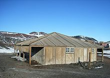 Wooden structure with door and two small windows. To the left is an open lean-to. In the background are partly snow-covered mountains