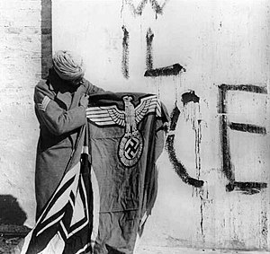 "India in World War II - A Sikh soldier (of the 4th Division (the Red Eagles) of the Indian Army, attached to the British Fifth Army in Italy) holding a captured swastika flag after the surrender of Nazi German forces in Italy. Behind him, fascist inscriptions on the mural says VIVA IL DUCE, ""Long live the Duce"" (Benito Mussolini). Photo circa May 1945"
