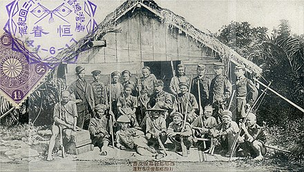 Commander-in-chief Saigo Tsugumichi (sitting at the center) pictured with leaders of the Seqalu tribe. Soldiers of the Japanese expedition in Taiwan.jpg