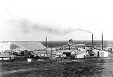 A black and white photograph of a busy mine with several smoking chimneys and industrial buildings