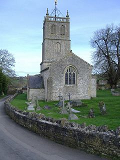 Gray building with arched windows. Square tower surmounted by a weather vane. Gravestones and crosses in grass in the foreground separated from the road by a stone wall.