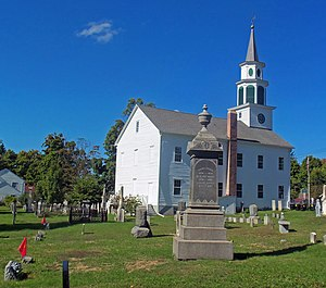 A white church, seen from the side slightly to its rear, with a cemetery in front