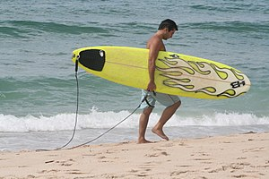 A surfer carries a surfboard along the beach
