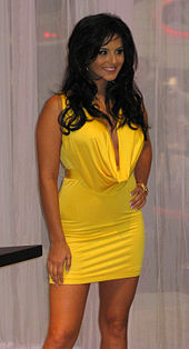 A woman shown in three-quarter length, wearing a yellow mini-dress