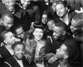 Surrounded by recruits, Marva Louis, wife of champion Joe (Louis), takes time out from a tour of nightclubs... - NARA - 535855.tif